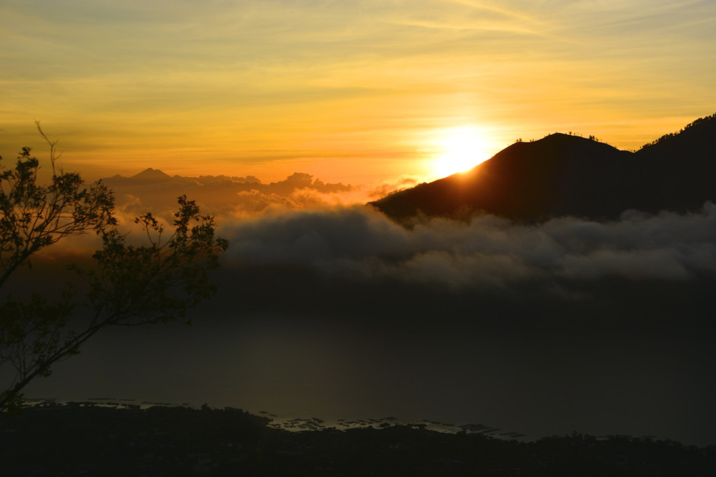 Sunrise behind Bali's highest peak Gunung Agung (3148m). Gunung Rinjani (3726m) on neighboring Lombok in the distance.